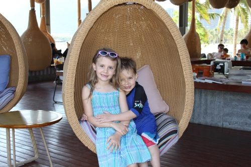 Isabelle and Oliver in the swinging bar seats by the beach.