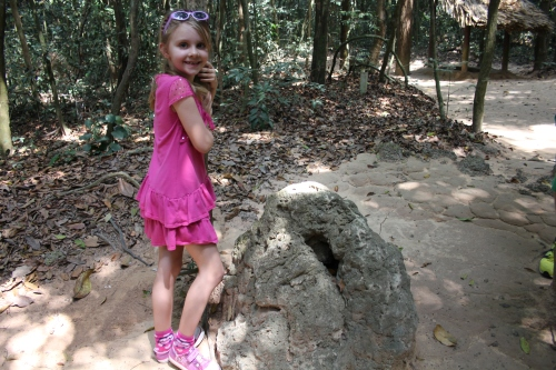 Isabelle standing by a termite hill.  Except, this is actually a clever disguise of a lookout for a tunnel.