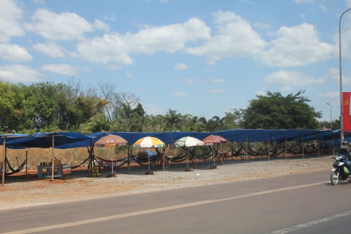 A rest area on the side of the road with hammocks for sleeping.  Another photo taken from our moving car!
