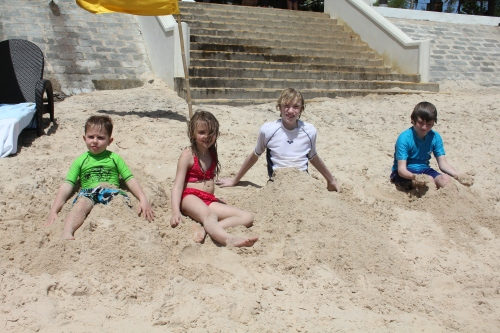 Burying each other in the sand at the beach.