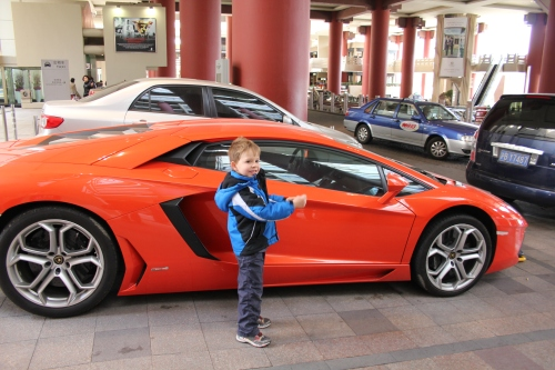 "Oliver is pretending to drive this flash car.  He is very impressed by fast, impressive vehicles and knows the names of all the fancy ones.  As Shanghai is full of ""new money"", we often see these types of cars around town."