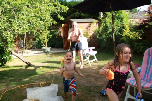 Grandad soaking the kids in the garden.