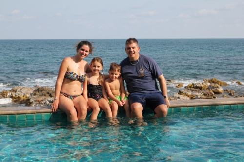 Family in the infinity edge pool at Kanda Residences.