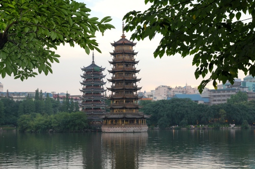 The late afternoon view of the sun and moon pagodas.  The Sun and Moon Twin Pagodas is situated in Shanhu (Shan Lake).  The word sun and moon in Chinese character written together mean brightness.  Some say it symbolises the future of Guilin is bright.  The Sun Pagoda is constructed with copper, it has 9 floors and reaches a height of 41 metres. The Moon Pagoda's is made of marble; it has 7 floors and measures 35 meters high. The two pagodas are connected via a tunnel at the bottom of the lake.