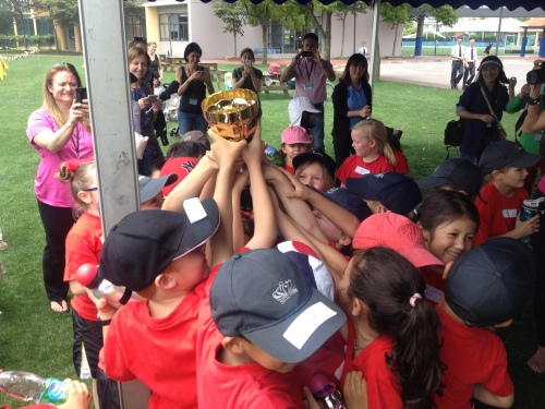 As many hands as possible trying to raise the cup for winning the Sports Day cup for their house.  Li House won the day for Infants!
